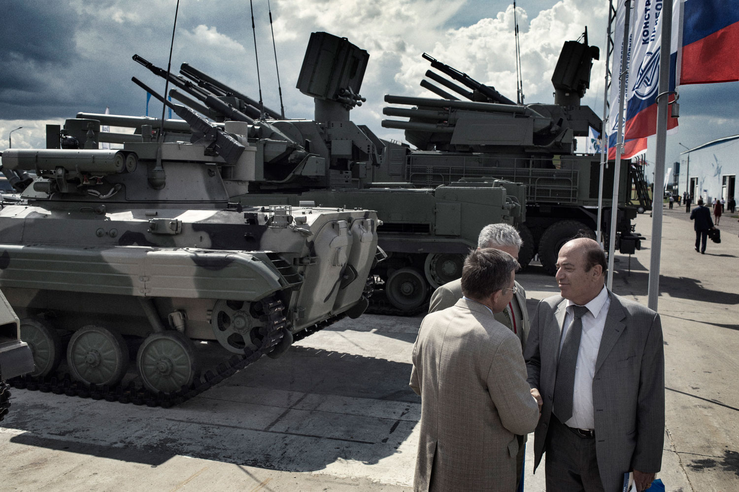 The head of the Syrian delegation to Russia's biennial arms bazaar shakes hands with a representative of Rosoboronexport, the Russian state weapons export monopoly.