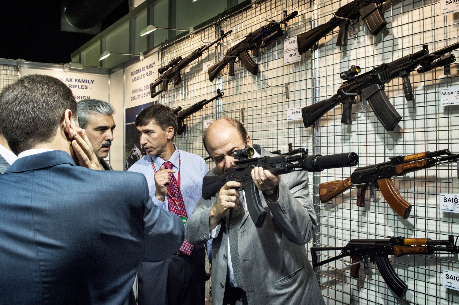 The head of the Syrian delegation to the arms bazaar tries out a new silencer-equipped Kalashnikov assault rifle.