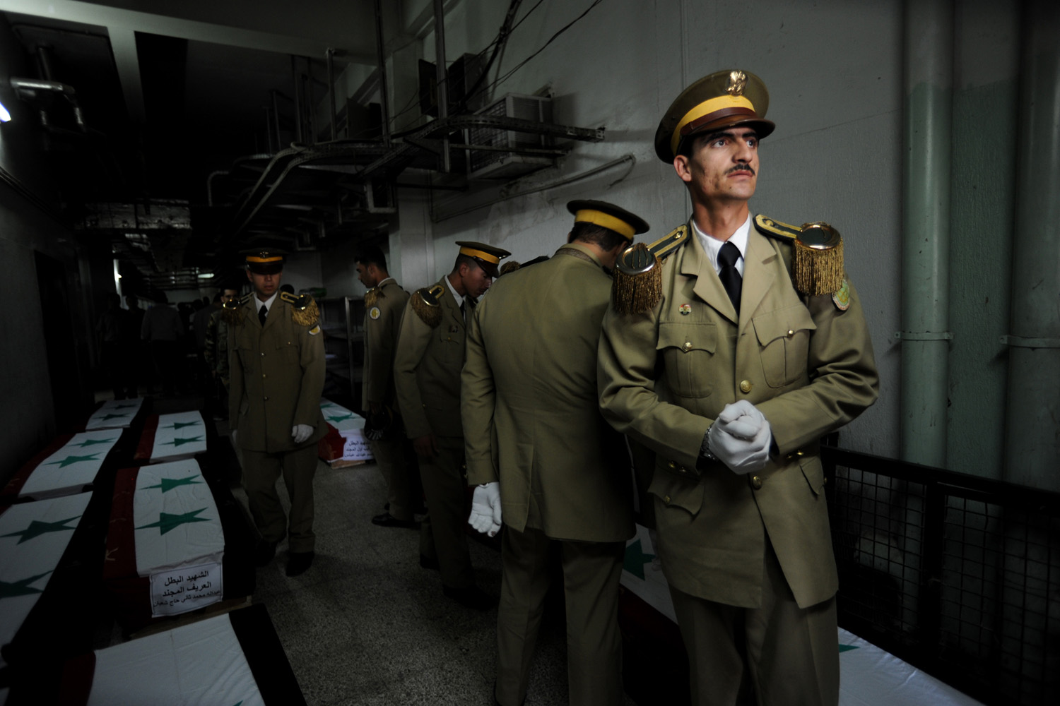 Kate Brooks                                A couple of days after I arrived in Damascus, I photographed a series of military funerals — 42 in total. Eight more men remained in cool storage at Tishreen Military Hospital for the next ceremonial conveyer belt. I can't claim to know what the man in white gloves was thinking when I took this frame, but he appears worried and concerned, as are all Syrians, about the number of coffins stacking up and what the future holds.                                                              When I was in Syria in June, I was told 100 soldiers and officers were dying each week in the conflict. To put that into perspective, at that rate, over the past year more soldiers may have died in combat in Syria than American soldiers in Iraq over a nine-year period. In considering the tally of this ongoing conflict, it's important to remember that military service is mandatory for all Syrian men.