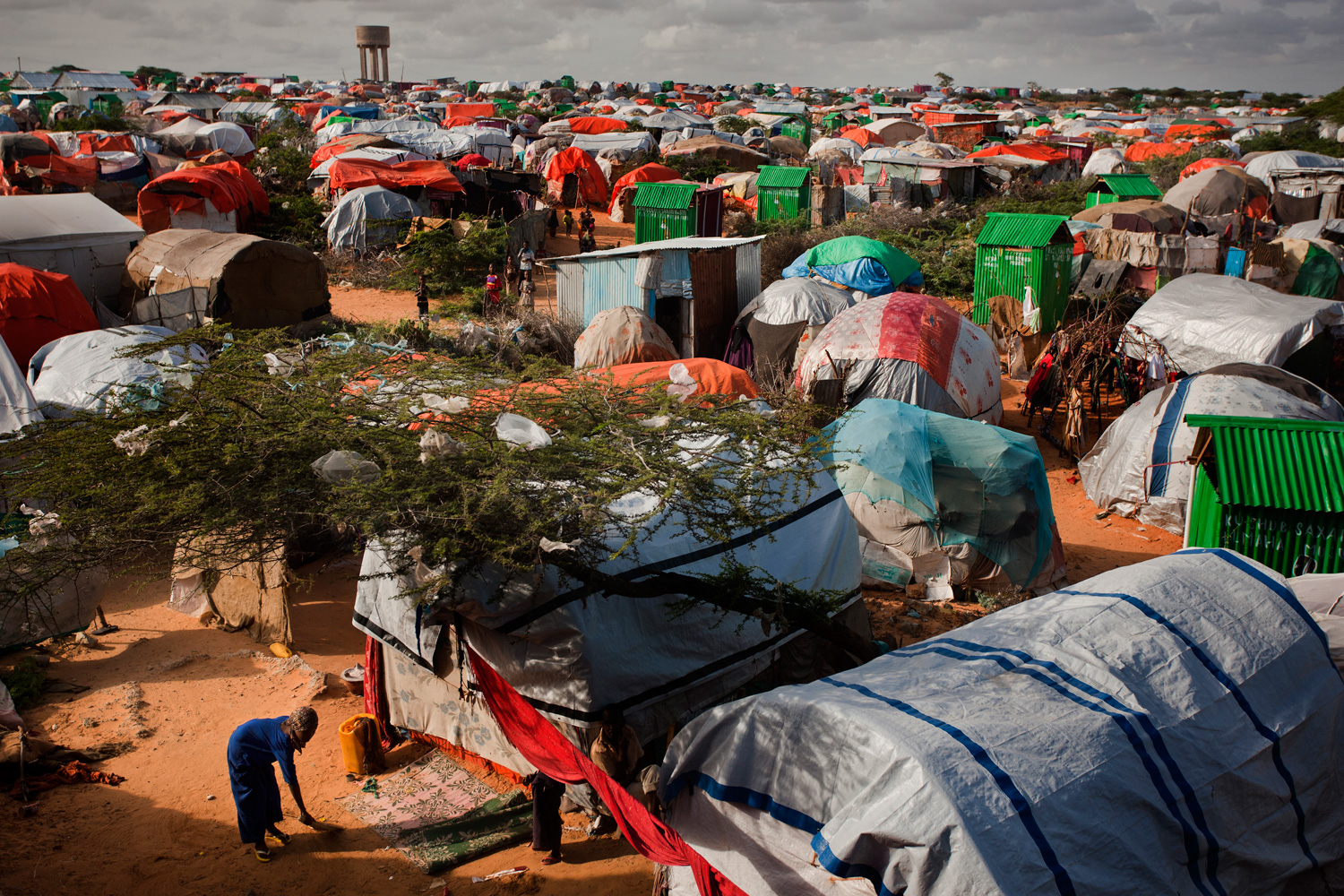 A young girl sweeps in front of her tent inside an overpopulated camp for internally displaced people in Mogadishu.