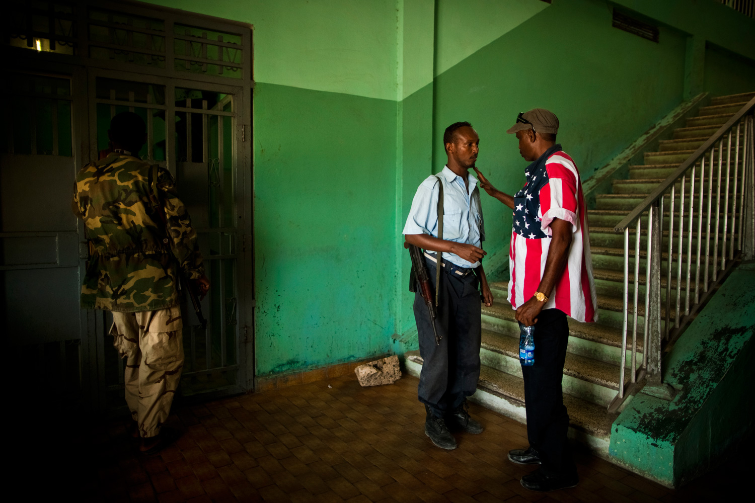 A Somali man wearing an American flag shirt talks to a policeman inside a building at the port in Mogadishu.
