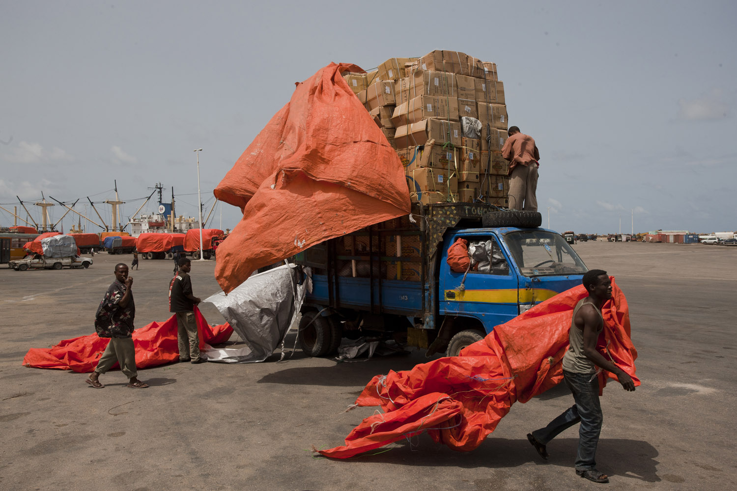 Somali men prepare to pack a truck full of goods at the port in Mogadishu.