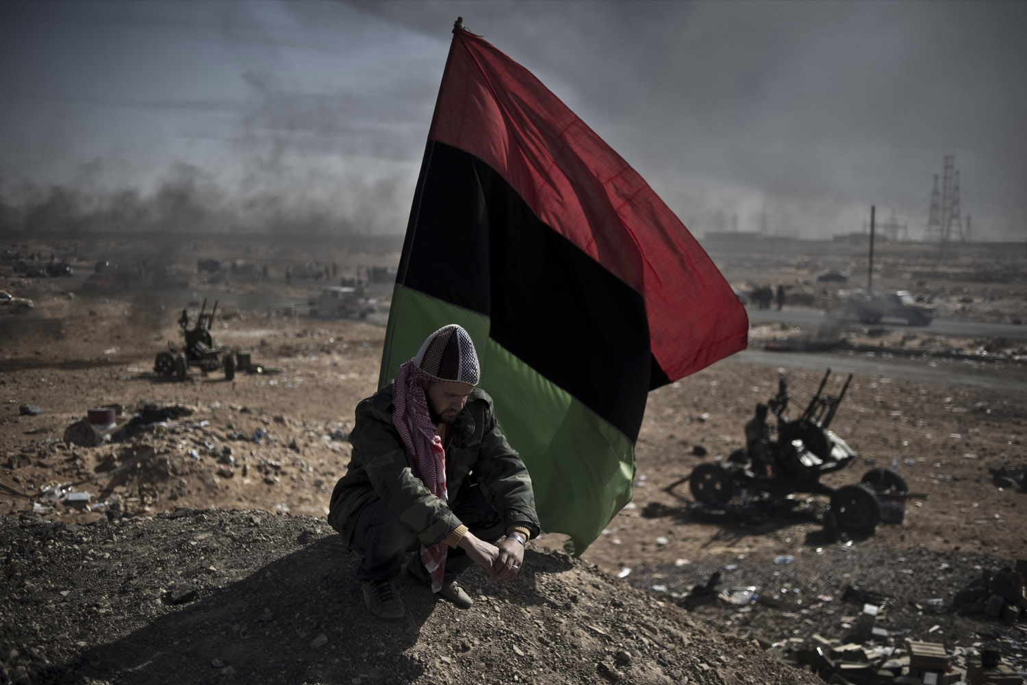March 11, 2011. An opposition fighter rests under a rebel flag in the middle of the battlefield in Ras Lanuf, Libya.