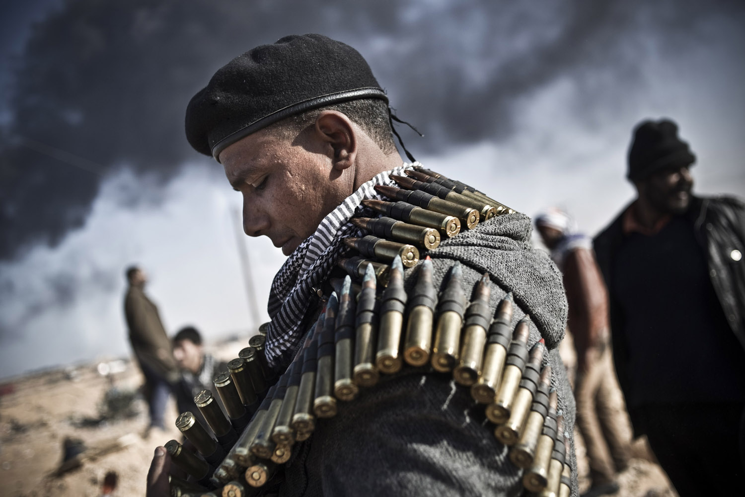 March 11, 2011. An opposition fighter with an ammunition belt in Ras Lanuf, Libya.