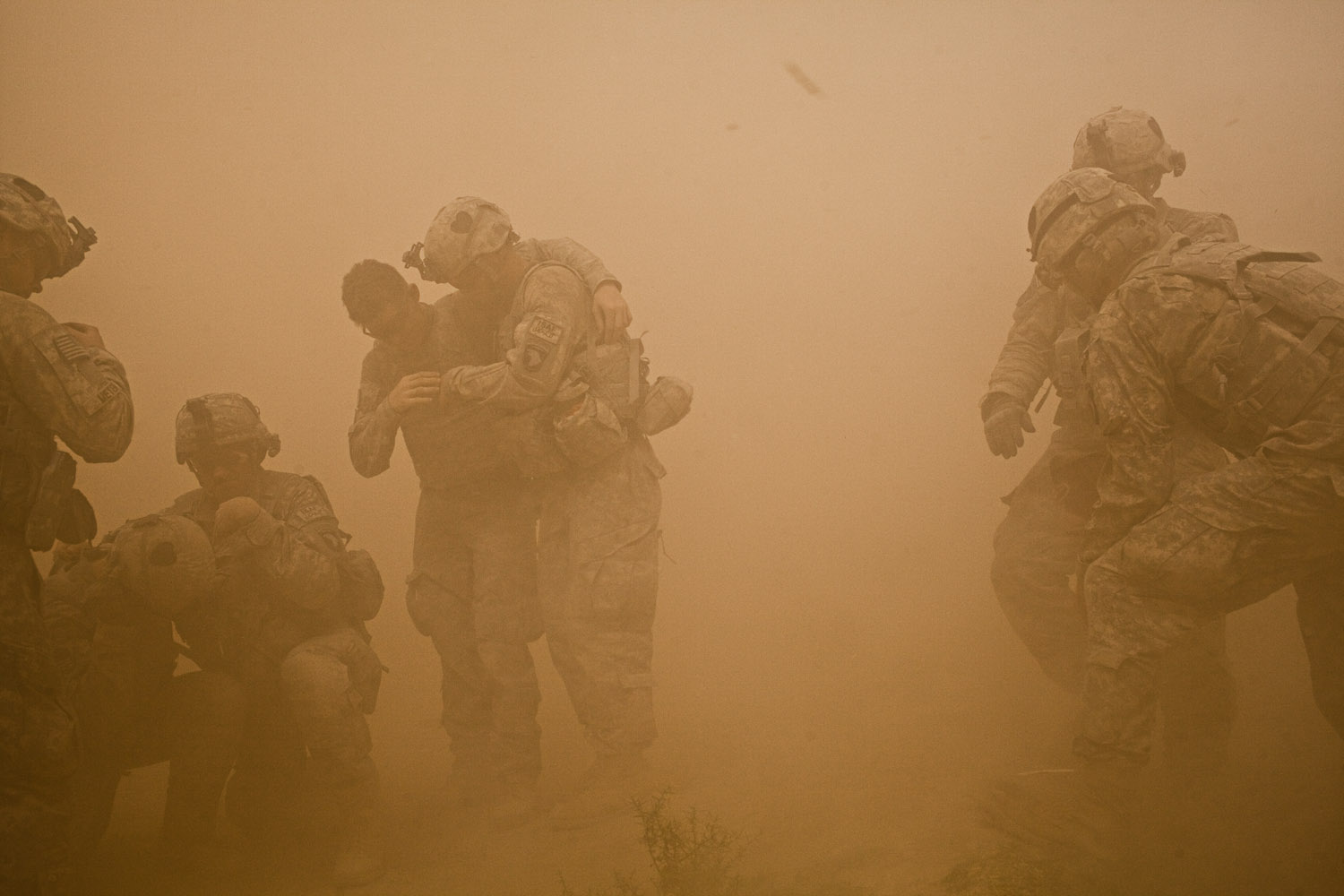 U.S. infantry soldiers shield themselves from dust and debris as a medevac helicopter lands to evacuate soldiers injured from two IED attacks during  Operation Clarksville  in Kandahar Province, Afghanistan. Oct. 9, 2010.