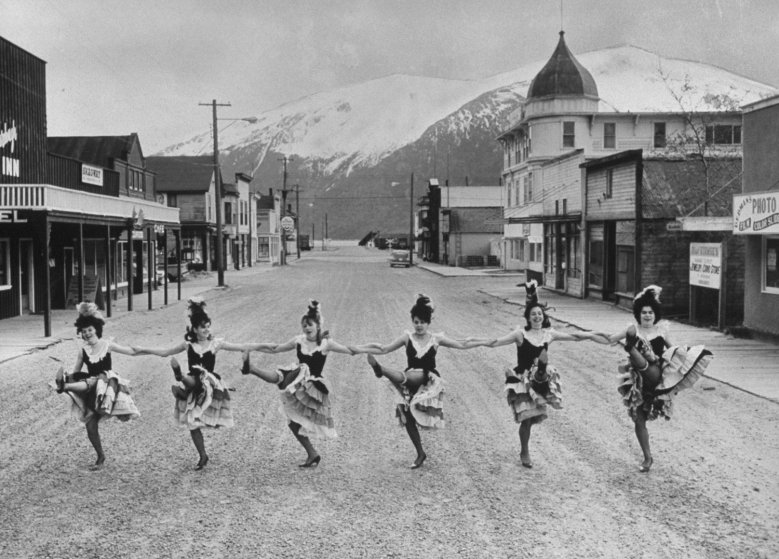 Skagway girls who dance in the Days of '98 show do the cancan in the middle of main street. The domed Golden North Hotel and false-front buildings date back to Klondike gold-rush days.