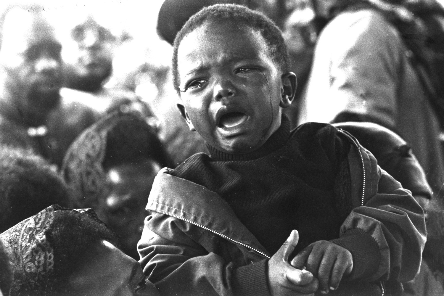 Little Samora, still in his mother's arms, sobs bitterly at the side of his father's grave. The agony of his loss is unclear but the agony of the moment was real enough. 1977.