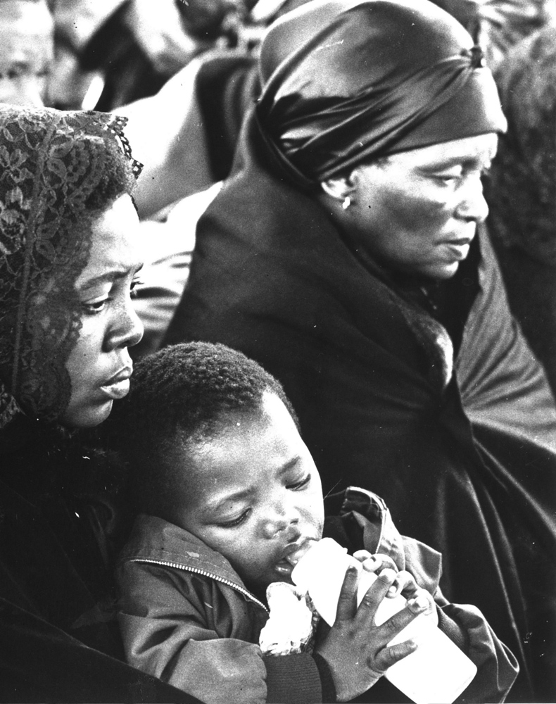 Samora and Ntsiki Biko. Little Samora clings to his bottle in the arms of his mother.  1977.