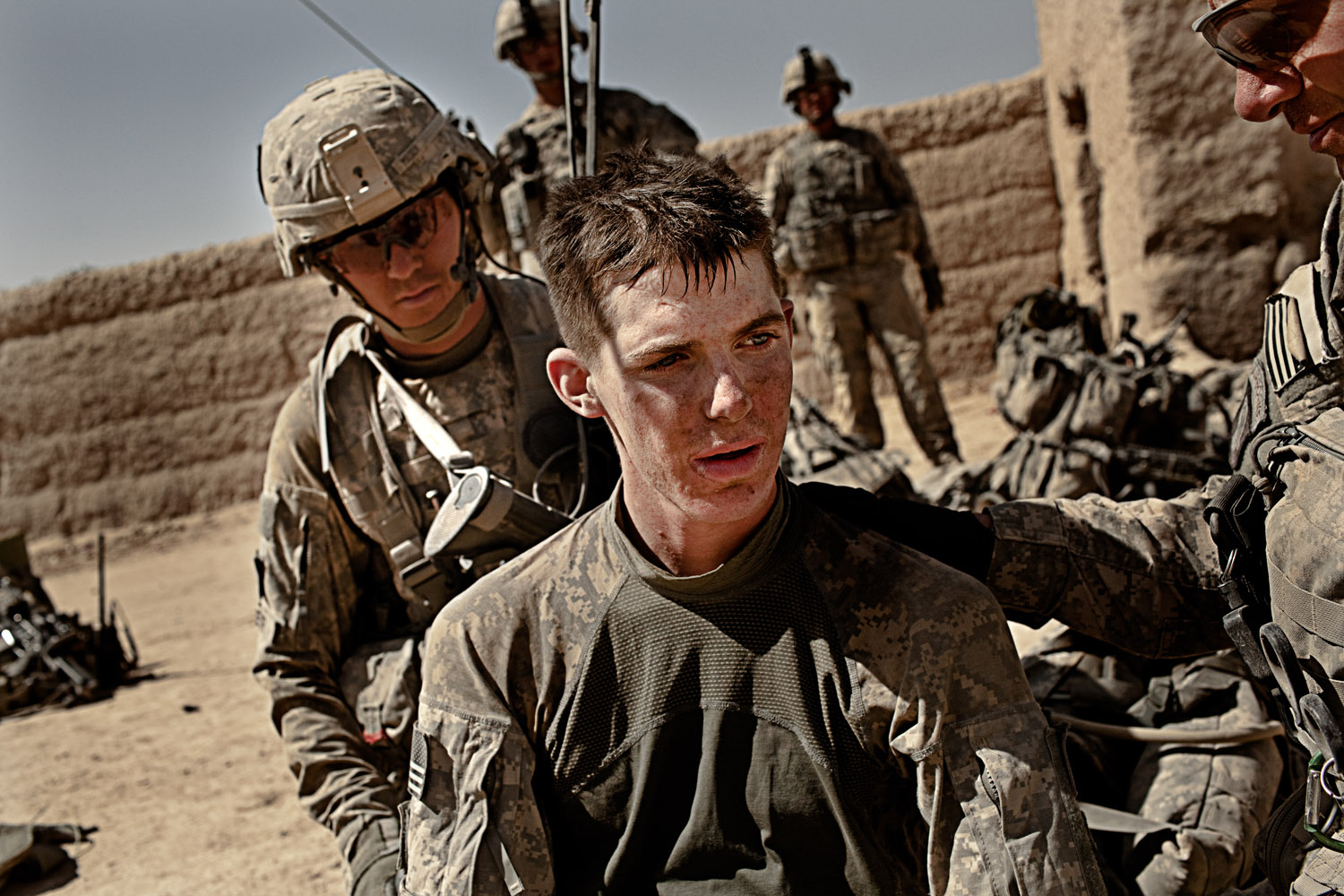 Private First Class Matthew Sharpe, 19, receives medical treatment from fellow soldiers after two IED attacks in Kandahar Province, Afghanistan. Oct. 9, 2010.