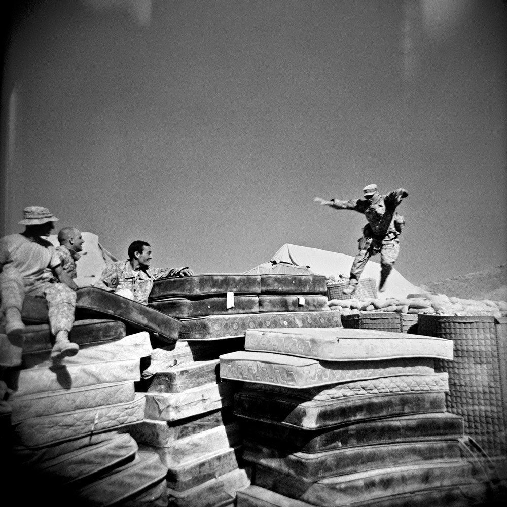 Soldiers watch Specialist Adam Ramsey (right) jump onto a pile of mattresses in the south of Logar Province, Afghanistan. September 2009.