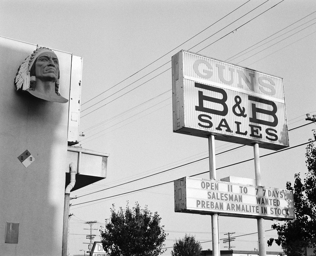 A sign advertising pre-ban Armalite assault-style weapons at B&B's gun store in Los Angeles. B&B's sales increased following the widely-publicized North Hollywood shootout, where Los Angeles police officers were outgunned by two heavily armed bank robbers protected by body-armour. A group of LAPD officers rushed from the siege to B&B's gunstore, borrowing M-16 assault rifles and pump-action shotguns with hundreds of rounds of ammunition before returning to the crime scene and killing the besieged robbers with the unofficial firearms.