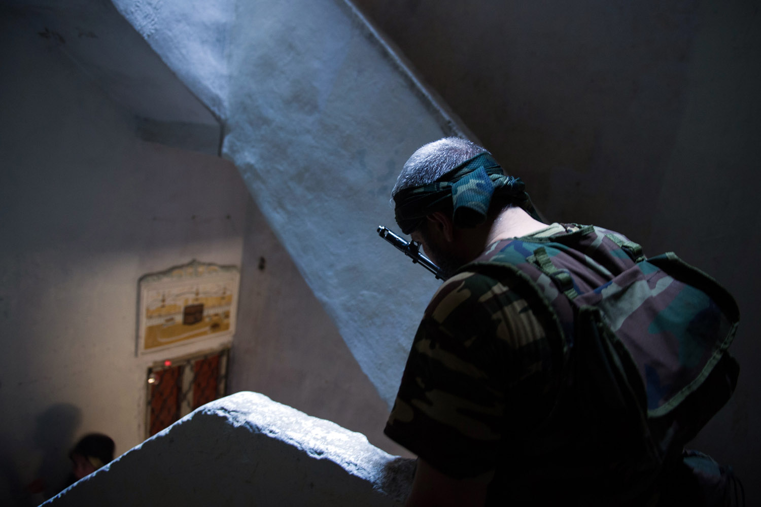 Aug. 10, 2012. A rebel from the Free Syrian Army (FSA) stands in the stairwell of a building being used as an access route in the Salaheddin district of the northern restive city of Aleppo.