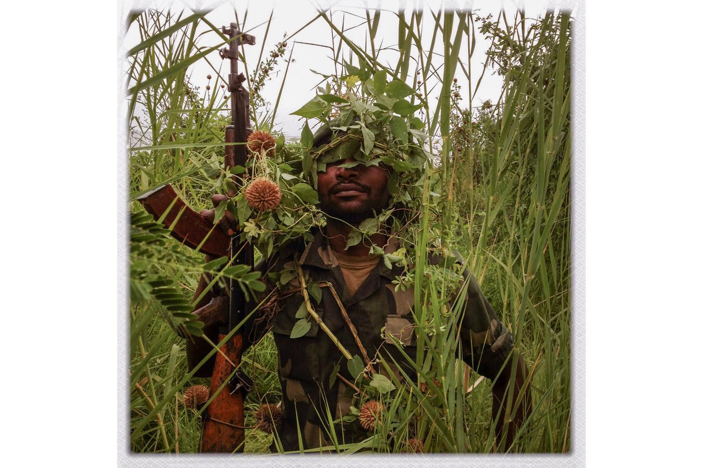An FARDC soldier poses for a portrait by Lake Kivu.