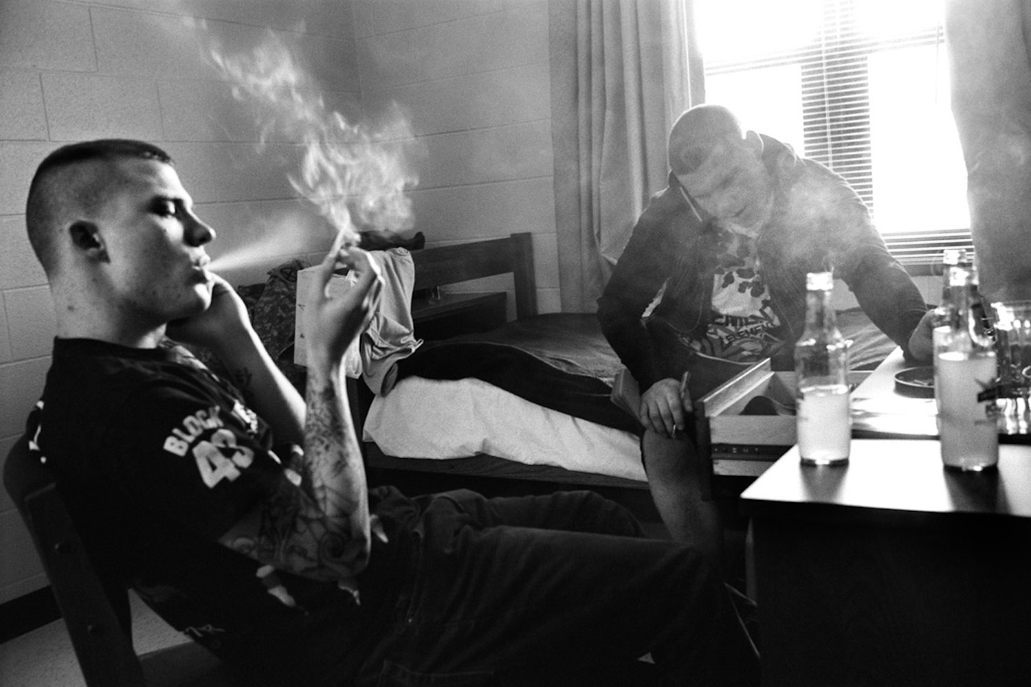 Specialists Ryan Cooley (left) and Adam Ramsey (right) smoke cigarettes in the infantry barracks, which houses unmarried soldiers, at Fort Drum, N.Y.  January 2010.