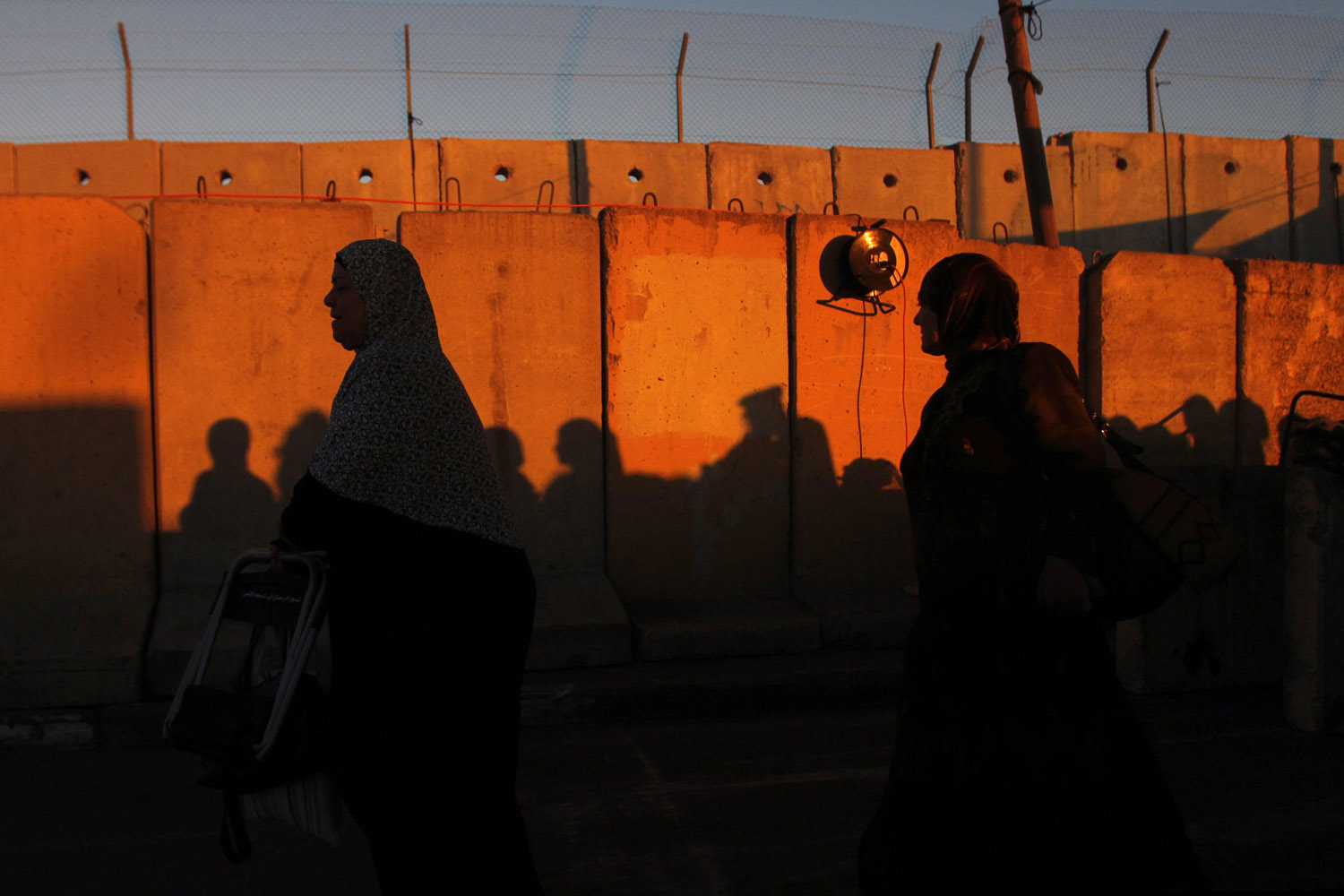 Aug. 10, 2012. Palestinian women walk past a section of Israel's controversial barrier at Qalandiya checkpoint outside the West Bank city of Ramallah.