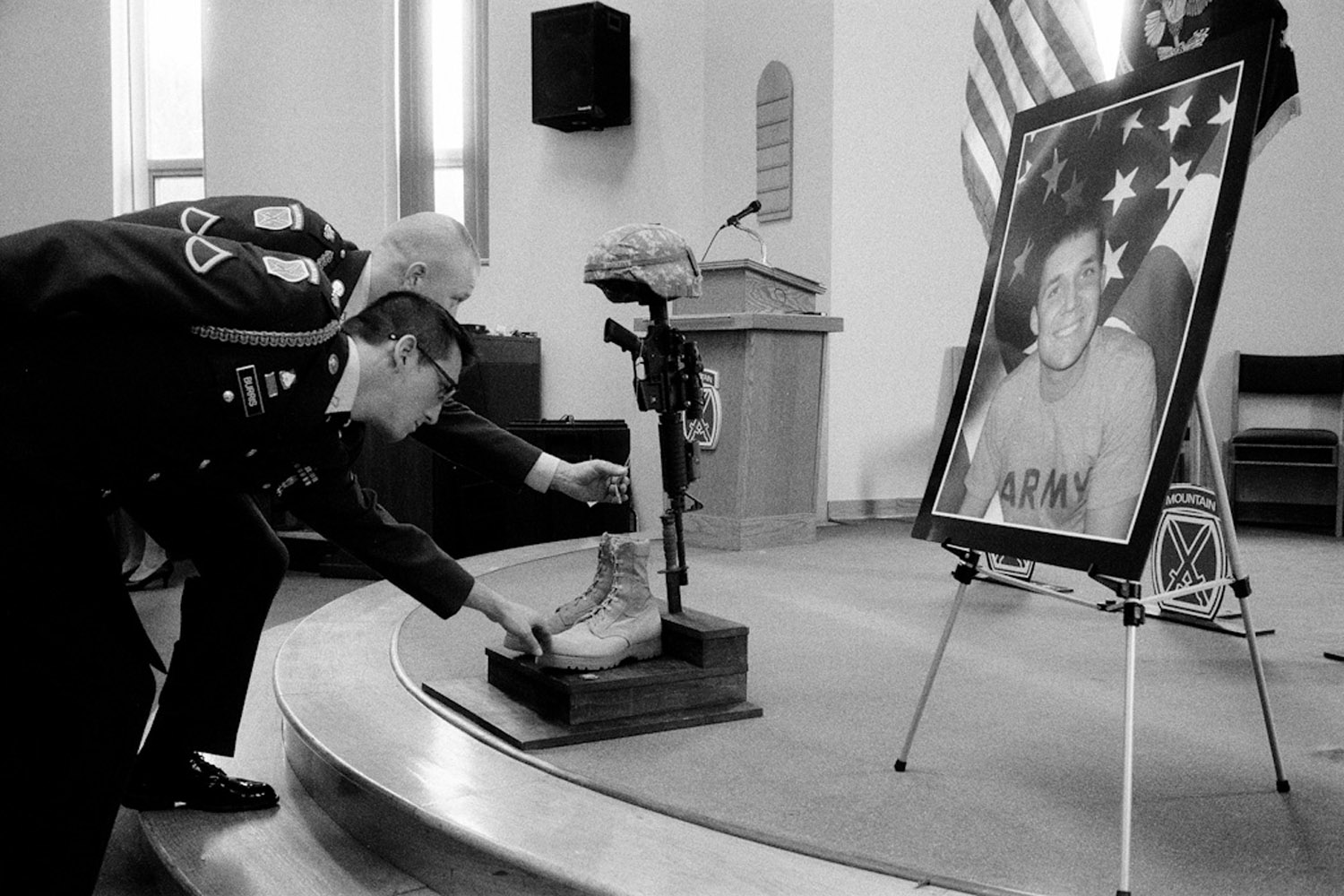 Two soldiers touch the dog tags of Staff Sergeant Cody Anderson at his memorial at Fort Drum, N.Y. January 2010.