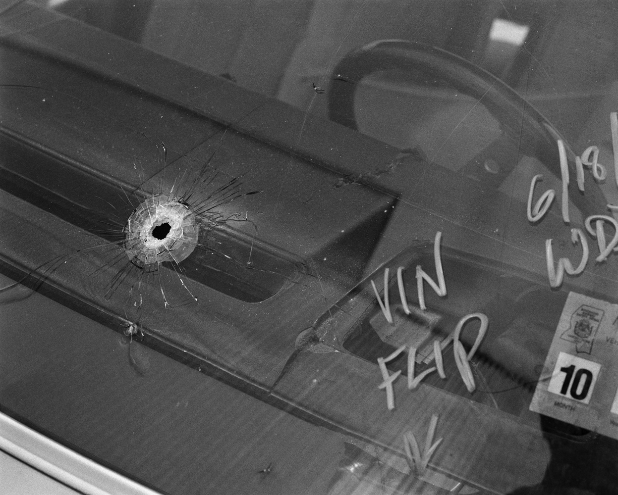 A bullet hole in a car windscreen. The owner of the vehicle saw two young men attempting to steal his car from his driveway. He opened fire on them from his lounge with a high-velocity deer-hunting rifle, killing one man and wounding the other. Police valued the car at $900.