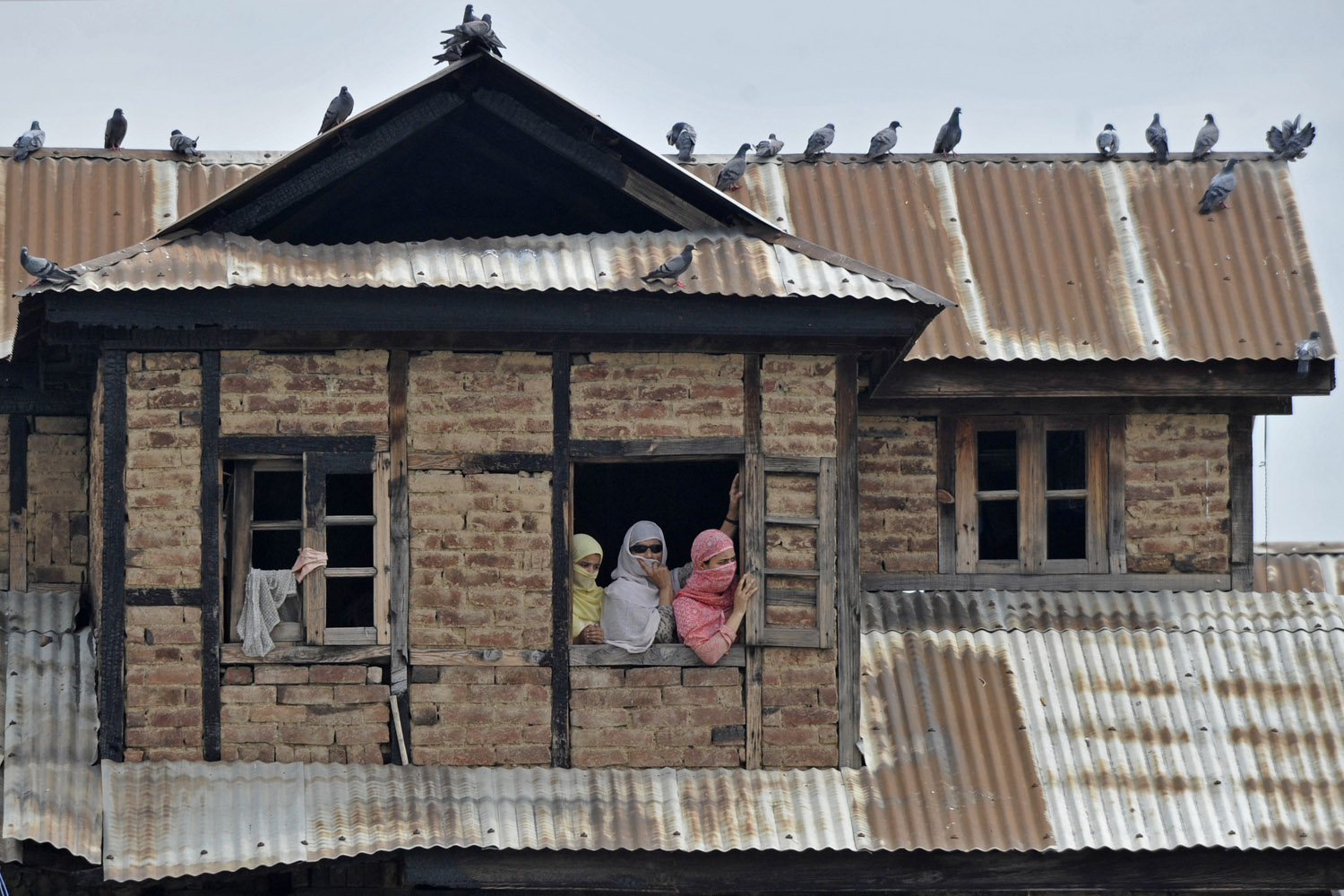 Aug. 10, 2012. Kashmiri Muslims look on from a window as an unseen custodian displays a holy relic in Srinagar, India.