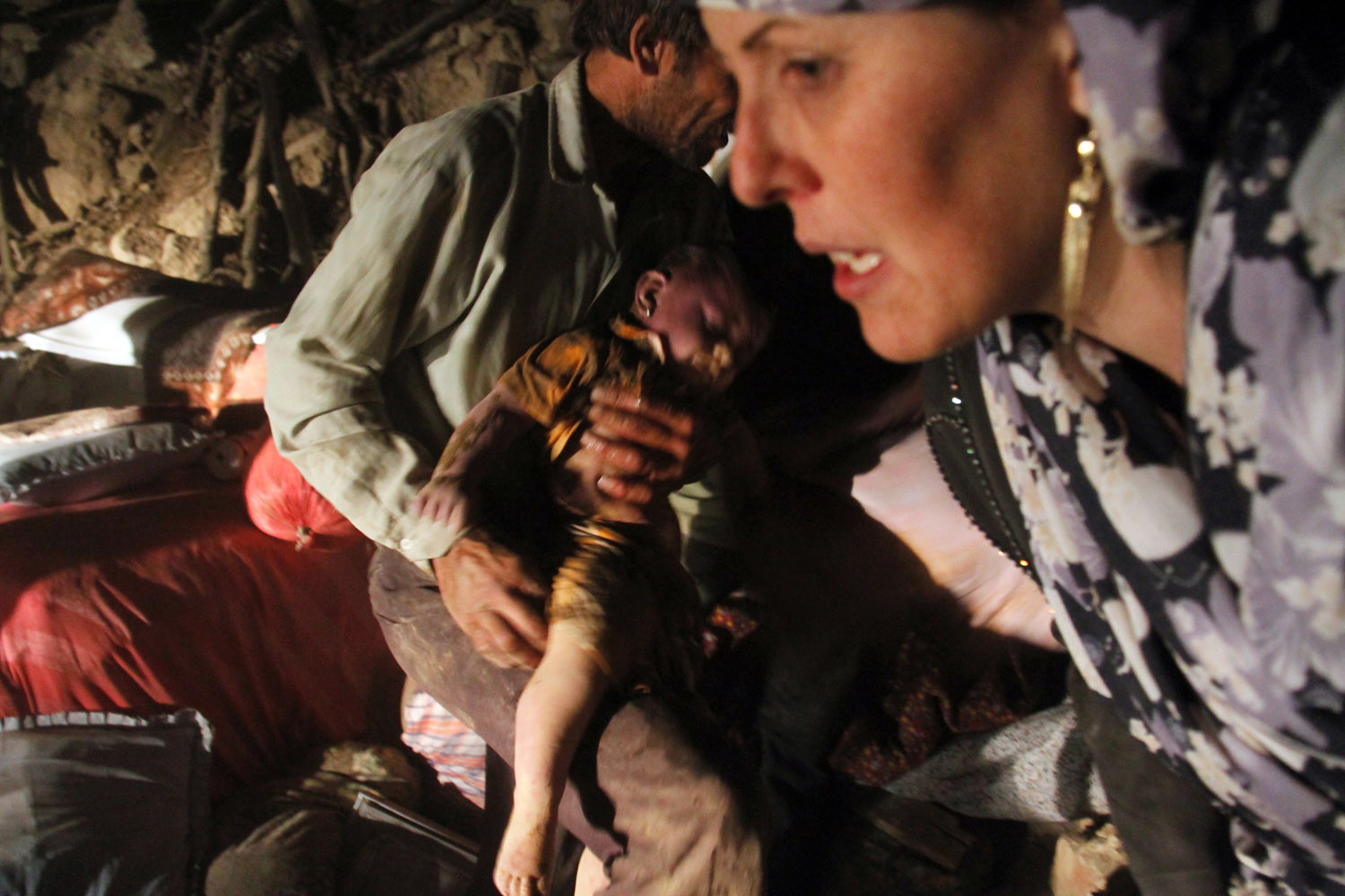 Aug. 11, 2012. Iranian residents try to rescue a child from the rubble in Sourmah village, near the town of Varzaqan, after two earthquakes hit northwestern Azarbaijan province in Iran.