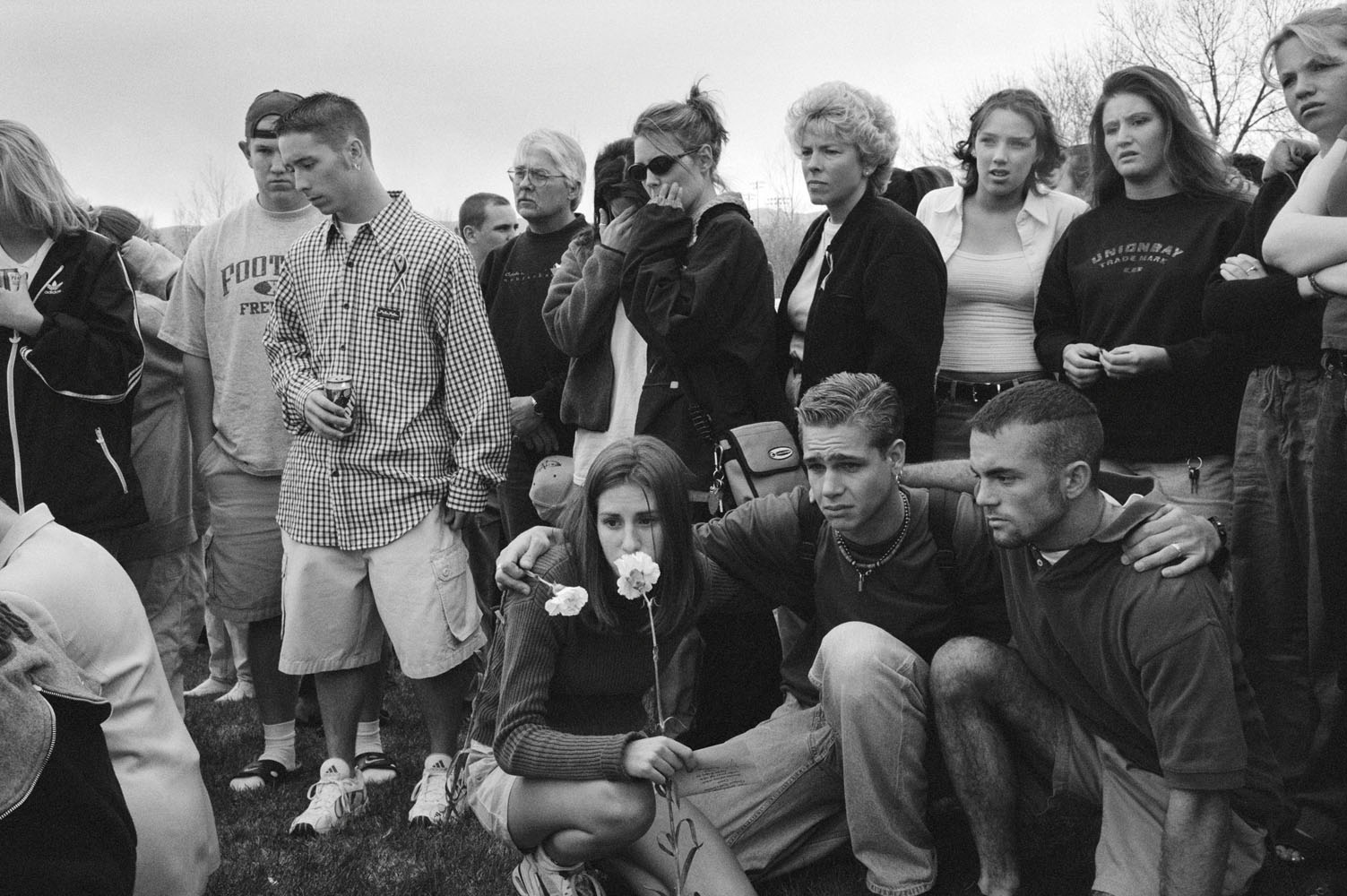 The day after the massacre, Columbine High School students gather outside their school to pray and place flowers on the ground. Many just wander among the tributes crying, trying to make sense of what has happened.