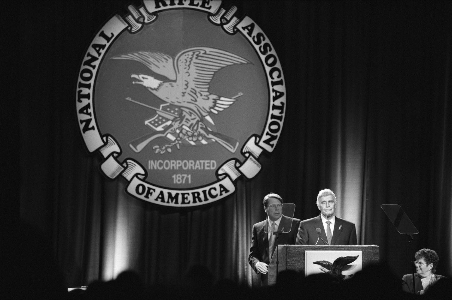 Charlton Heston, president of the National Rifle Association (NRA), addresses a crowd of 2,000 pro-gun members at the Adam's Mark Hotel in Denver, while outside 8,000 demonstrators encircle the hotel to protest the timing of the NRA's annual meeting in the area only ten days after the local Columbine High School shooting rampage.