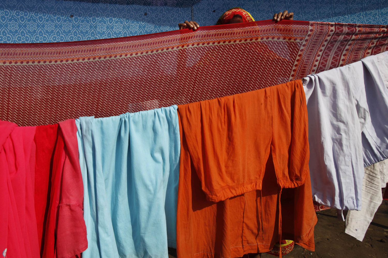 Aug. 12, 2012. A supporter of Indian yoga guru, Baba Ramdev, dries her clothes at the venue of an anti-corruption protest in New Delhi.