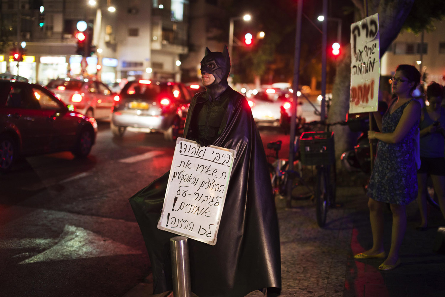 Aug. 12, 2012. An Israeli in a Batman costume holds a placard during a protest against war with Iran, outside the home of Israel's Defence Minister Ehud Barak in Tel Aviv.