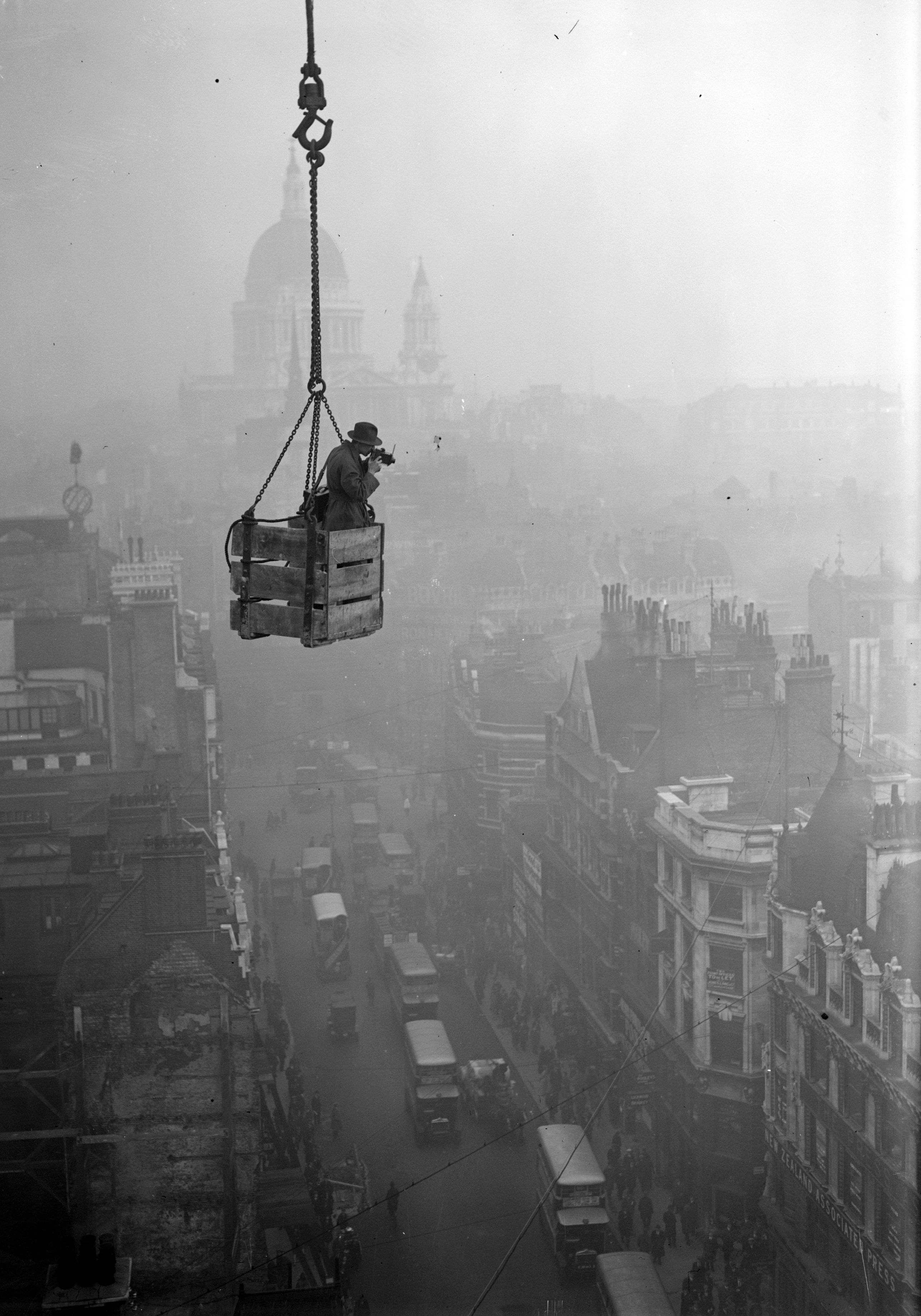 December 1929. A photographer dangles over Fleet Street, with St Paul's in the background.
