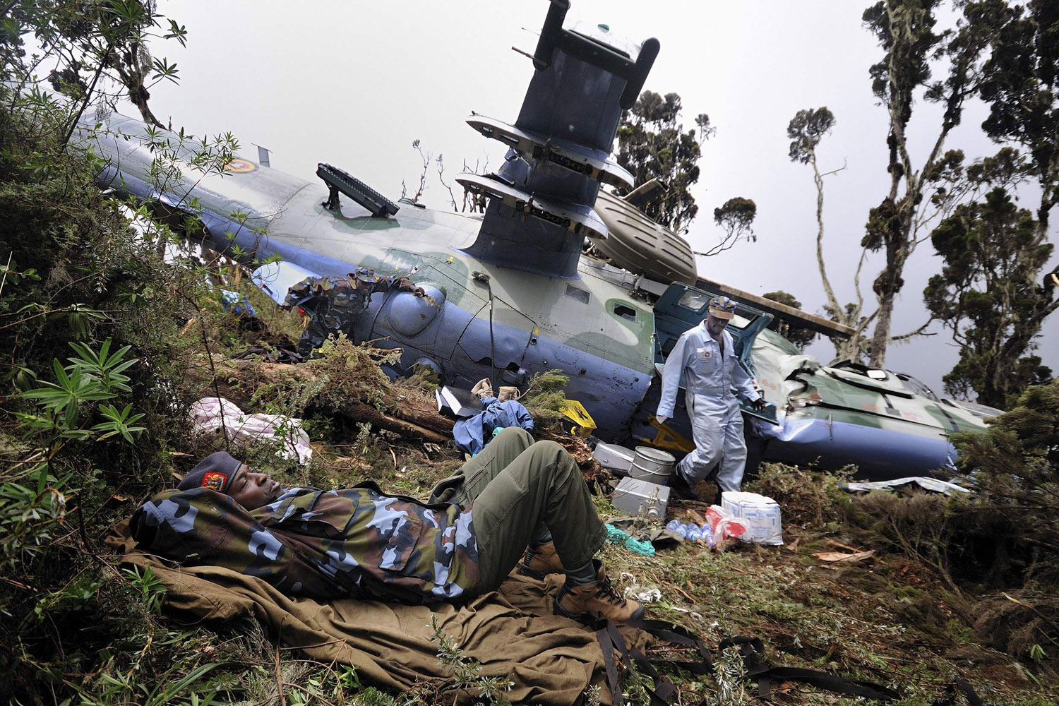 Aug. 13, 2012. The injured captain of a Somalia-bound Ugandan attack helicopter lies next to the crash site in Kenya.
