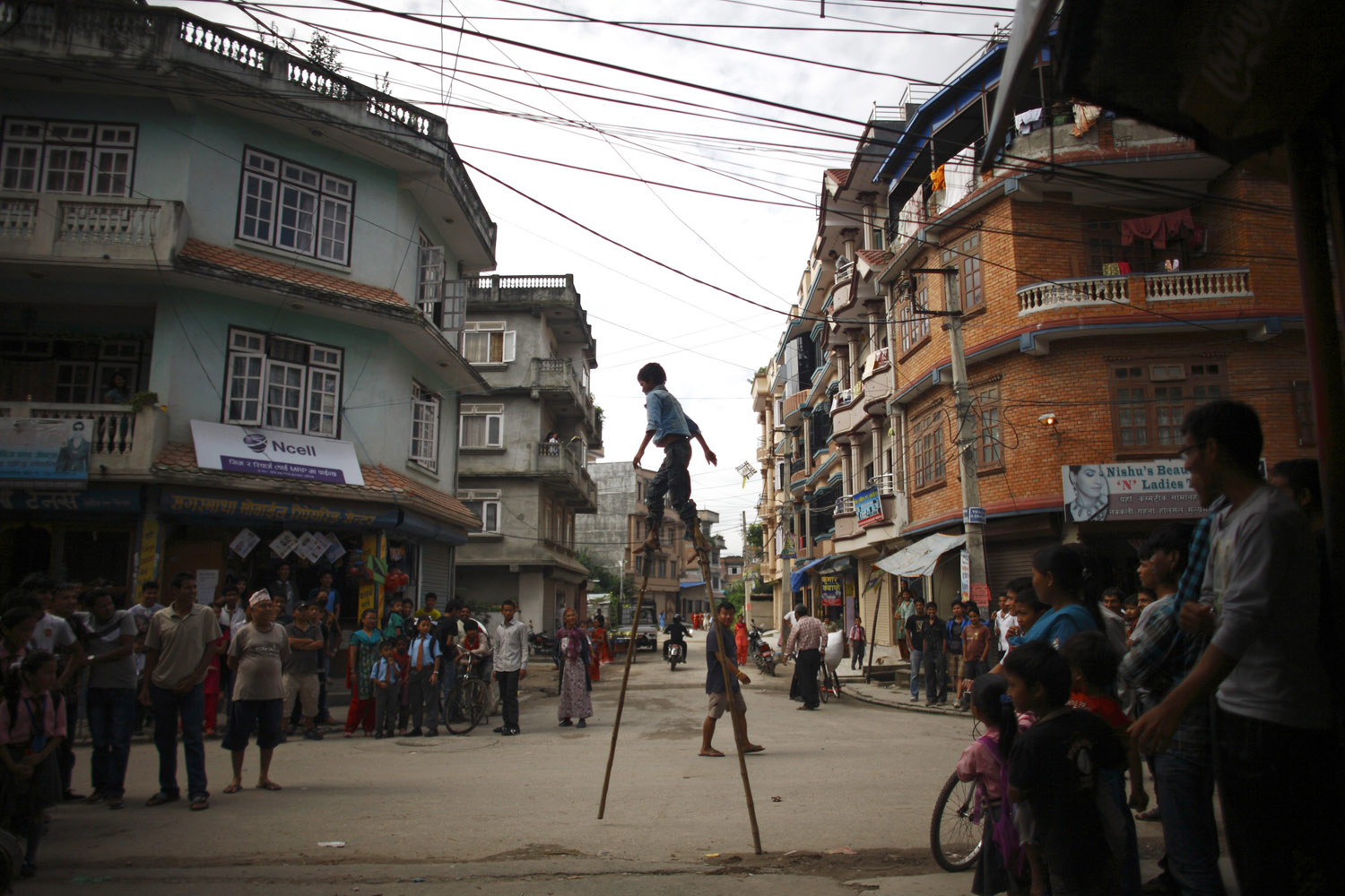 Aug. 13, 2012. A boy balances on wooden poles as he performs tricks to earn his living on a street in Kathmandu.