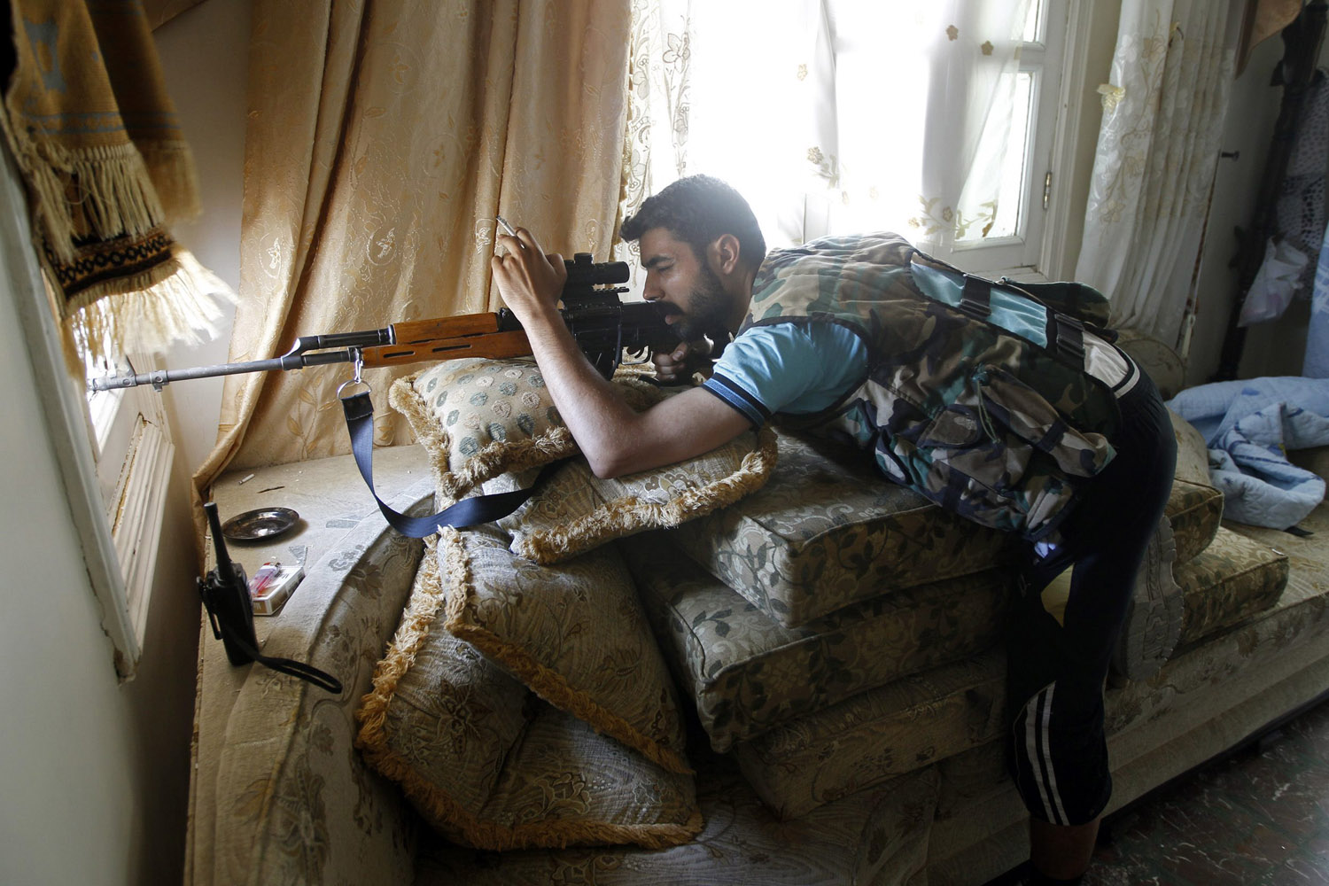 Aug. 13, 2012. A Free Syrian Army sniper looks through the sight on his rifle inside a house in Aleppo, Syria.