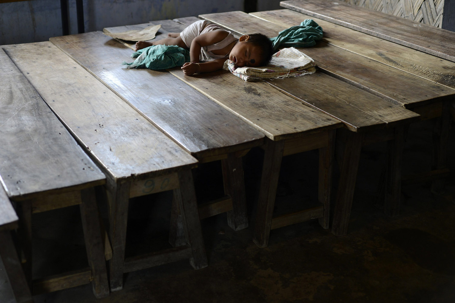 Aug. 13, 2012. A little girl takes a nap at Deborgaon relief camp in the riot affected Kokrajhar district of Assam state, India.