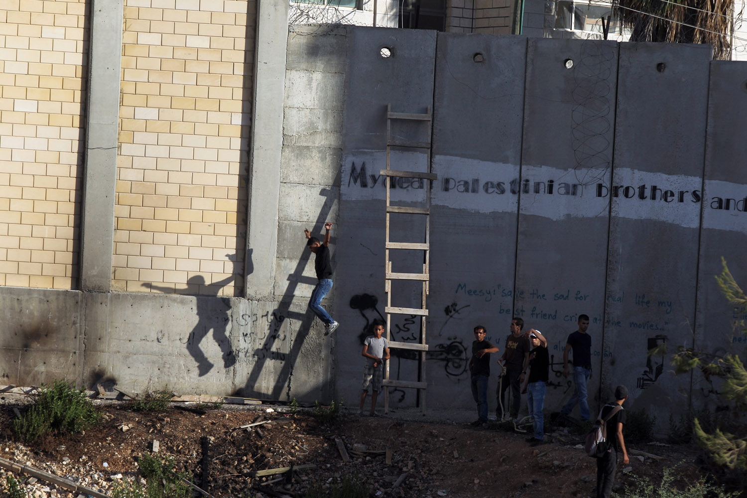 Aug. 14, 2012. Palestinian men use a ladder to cross over the separation wall, in the Palestinian town of A-Ram, North of Jerusalem, in the West Bank.