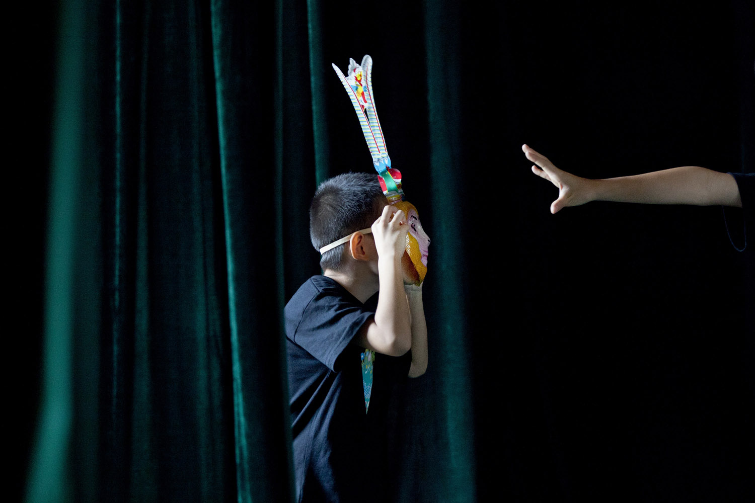 Aug. 14, 2012. A kid wearing a monkey mask plays in front of school children taking part in a summer camp training for the Chinese traditional Peking Opera in Beijing.
