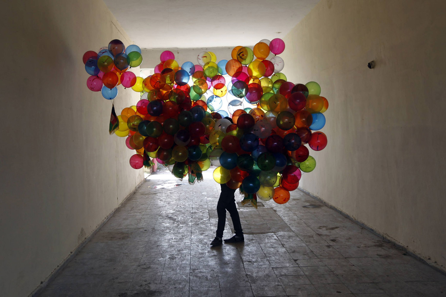 Aug. 14, 2012. A man holds balloons for sale near the National Stadium in Kabul.
