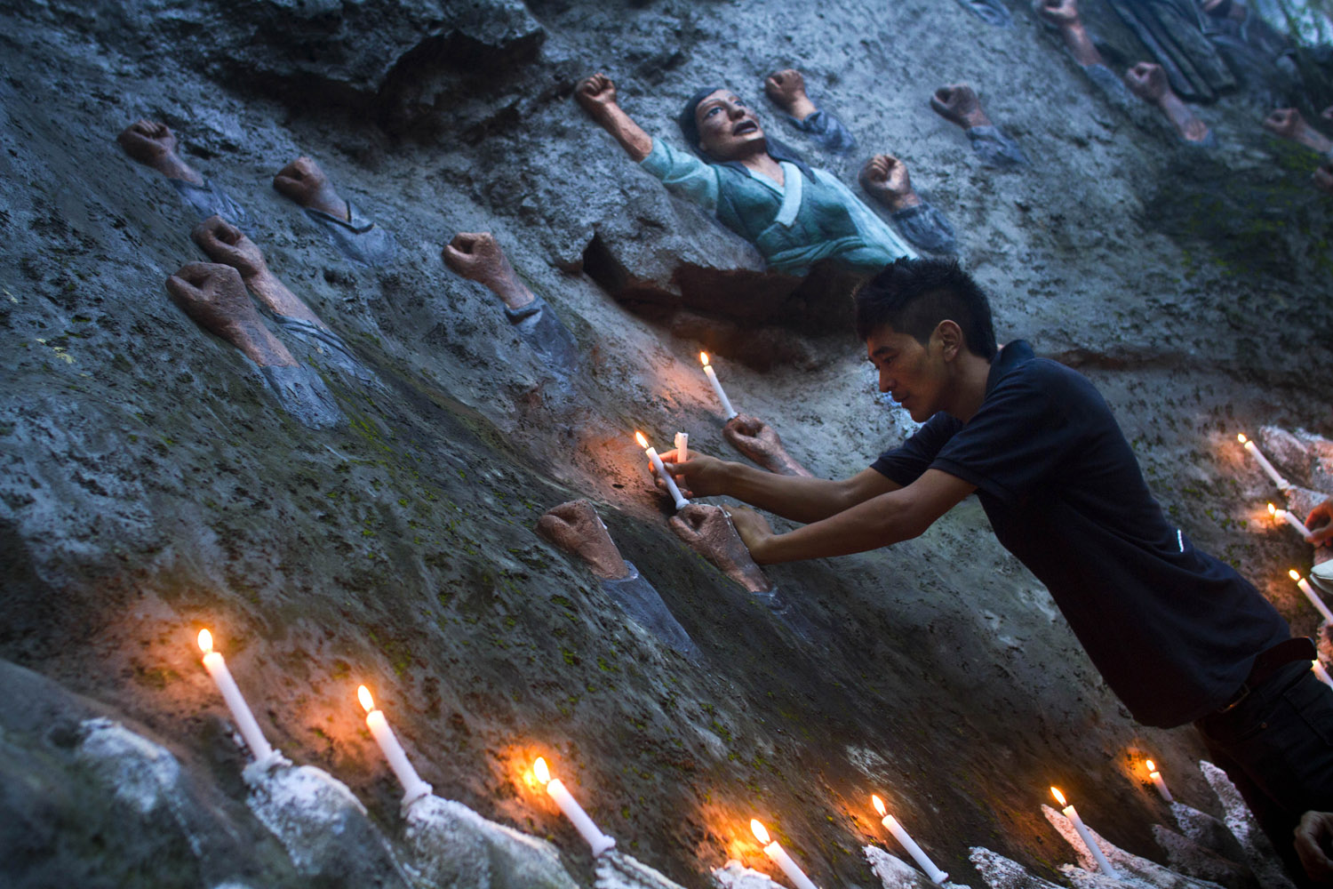 Aug. 14, 2012. An exiled Tibetan places candles on a sculpture known as Tibetan Martyrs' Wall, during a candlelit vigil in Dharmsala, India.