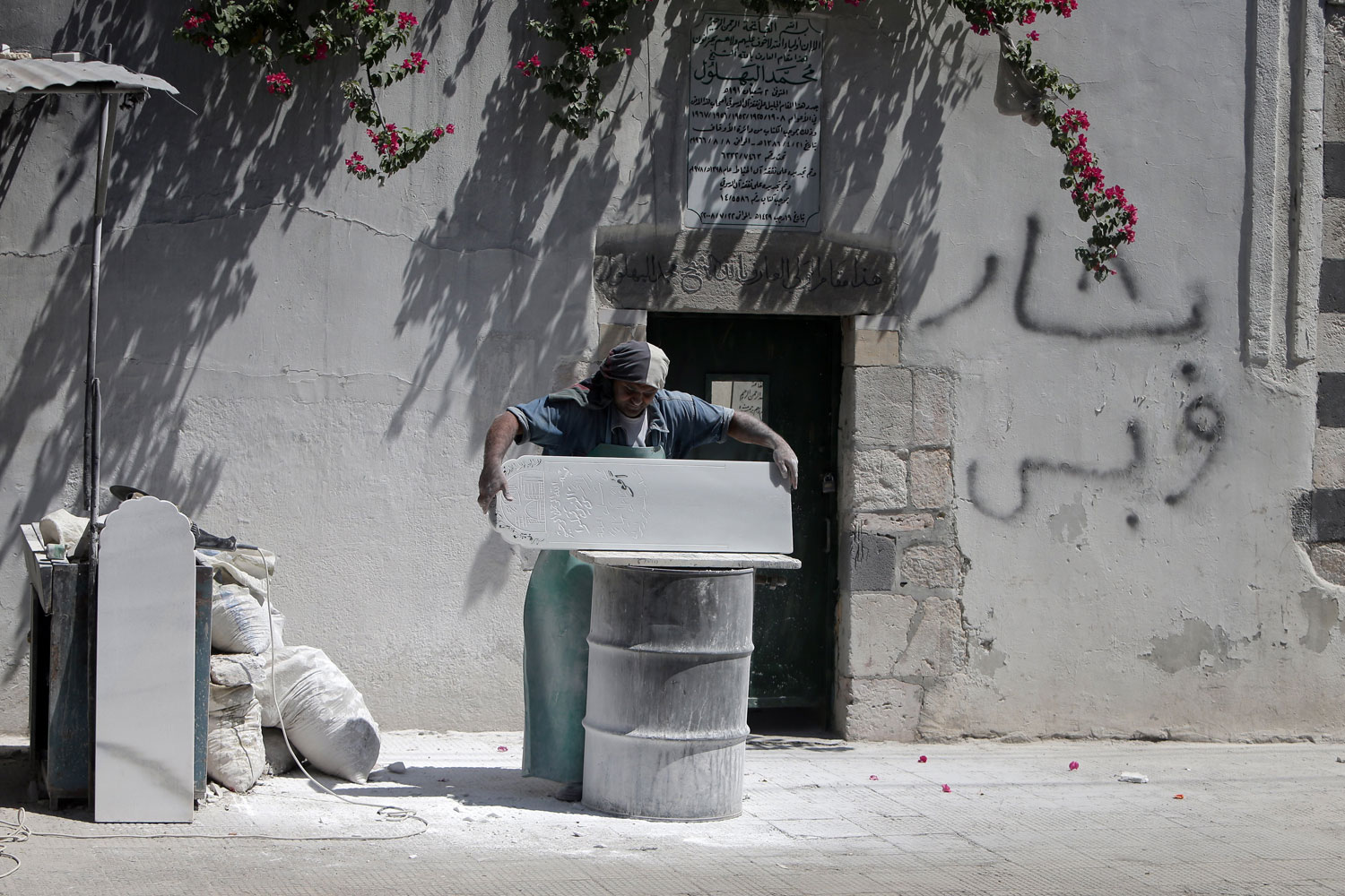 Aug. 28, 2012. A Syrian tombstone sculptor works at his workshop in Damascus.