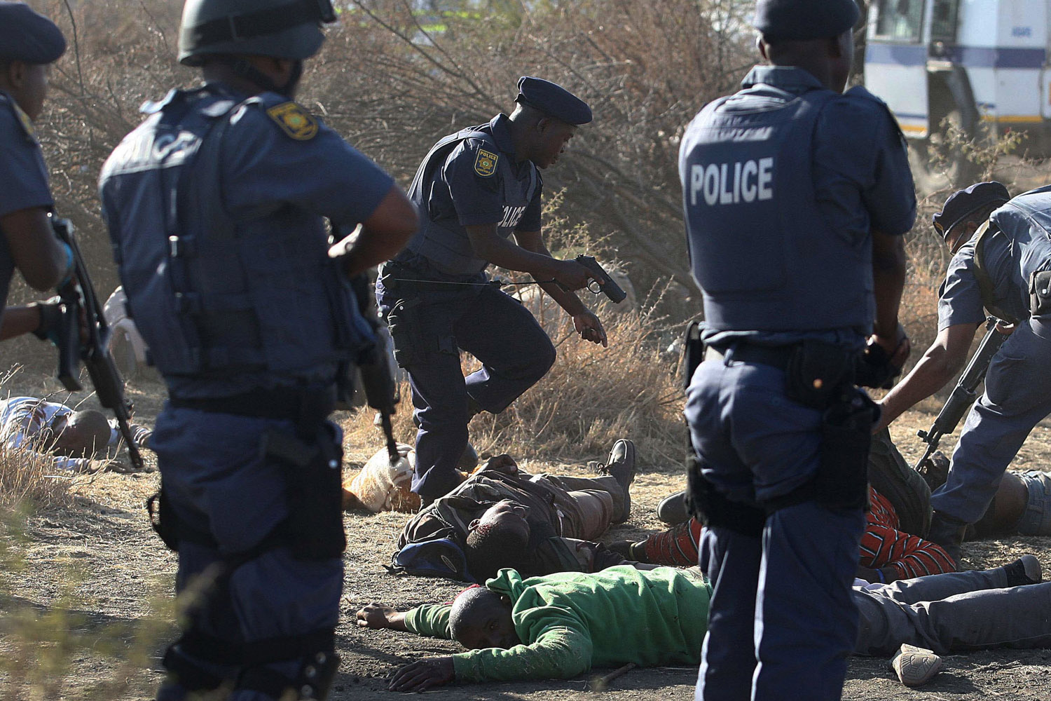 Aug. 16, 2012. Police surround the bodies of striking miners after opening fire on a crowd at the Lonmin Platinum Mine near Rustenburg, South Africa.