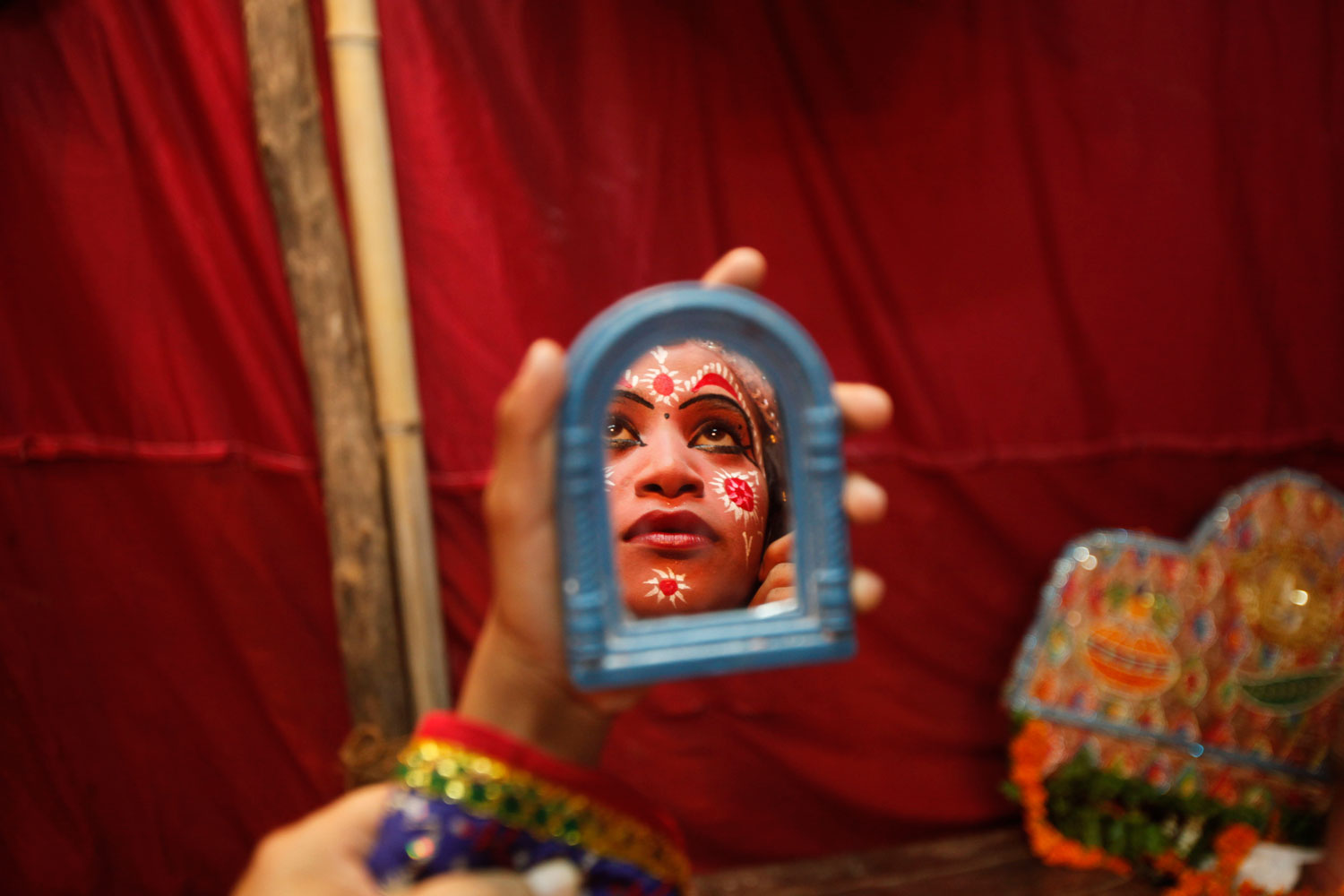 Aug. 10, 2012. A young Indian girl is reflected in a mirror as she gets ready to perform during Janmashtami festival celebrations in Mathura, India. Janmashtami is the festival that marks the birth of Hindu God Krishna.