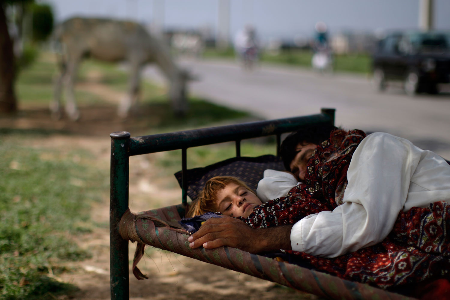 Aug. 16, 2012. A Pakistani man and his daughter sleep on a bed on a street median on the outskirts of Islamabad. Many Pakistanis sleep outdoors to escape the heat during the summer months.