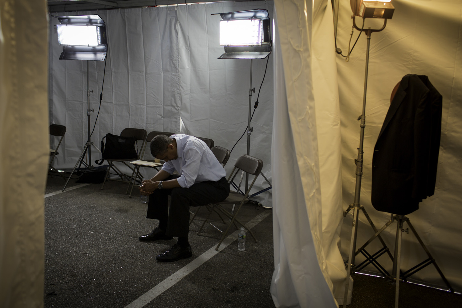 After a long day, President Obama waits in a tent before a rally at the Rochester Commons.