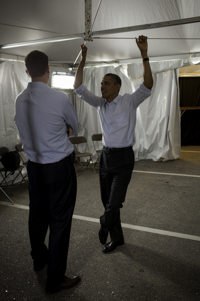 President Obama talks to White House Trip Director Marvin Nicholson in a holding tent before a rally at the Rochester Commons.