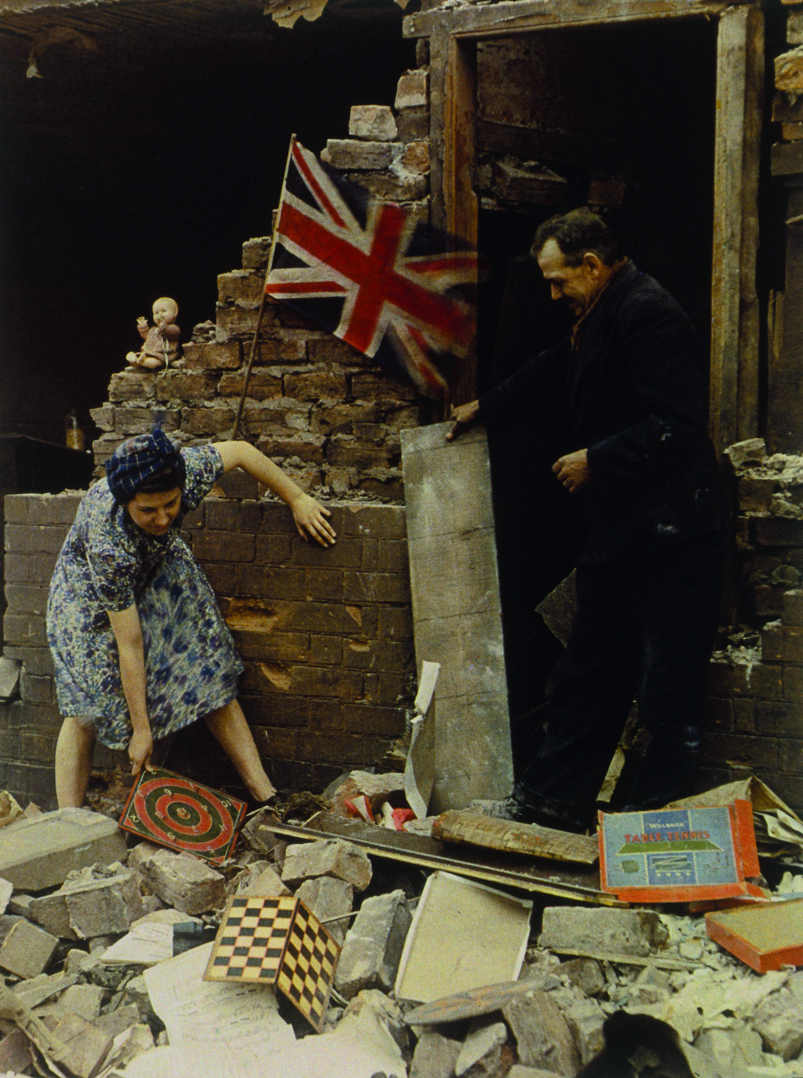 1939-1945. In what looks like a staged morale boosting image, a woman saves a board game from the bomb wreckage.