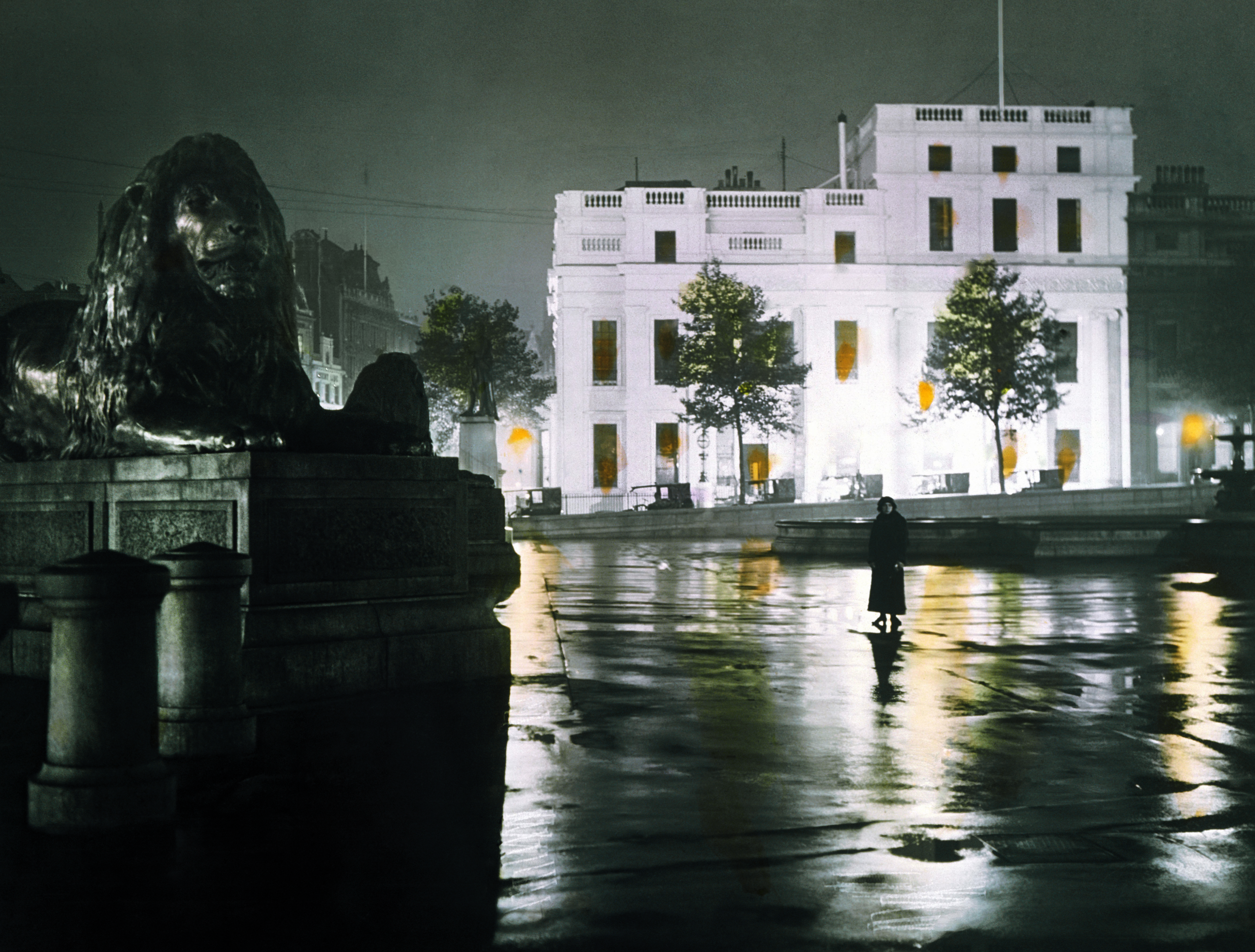 1910. A wet night in Trafalgar Square. A woman poses for a moody night-time shot. Despite the rain, a row of taxis wait on the west side of the square.