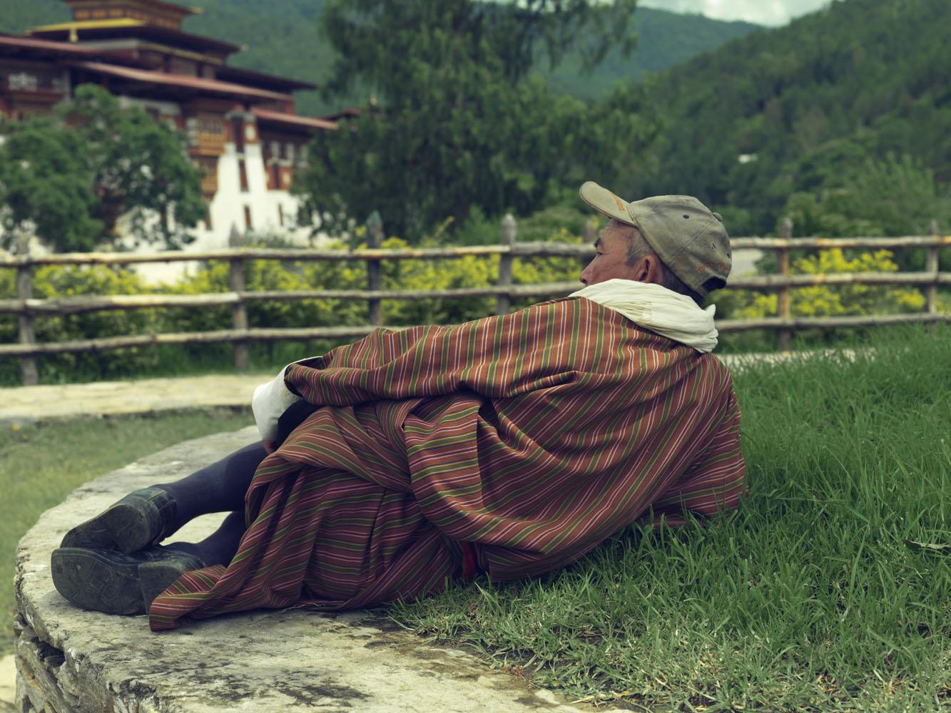 Karma Wangdi, a retired Government servant, rests next to the Punakha Dzong, Punakha.