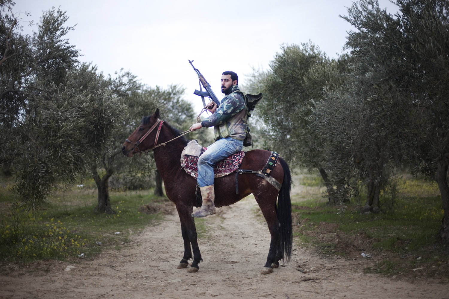 Giorgos Moutafis                                Shortly after entering al-Shatouria village, I met a group of FSA fighters in a grove of olive trees. There were about 10 men — just three of them were armed. They told me that they were planning on going back to the mountains close to the Turkish borders until they could better reorganize. I felt their depressed psychology and could sense their disappointment. Suddenly, one of them climbed up on his horse, holding his gun, and posed proudly in front of me.