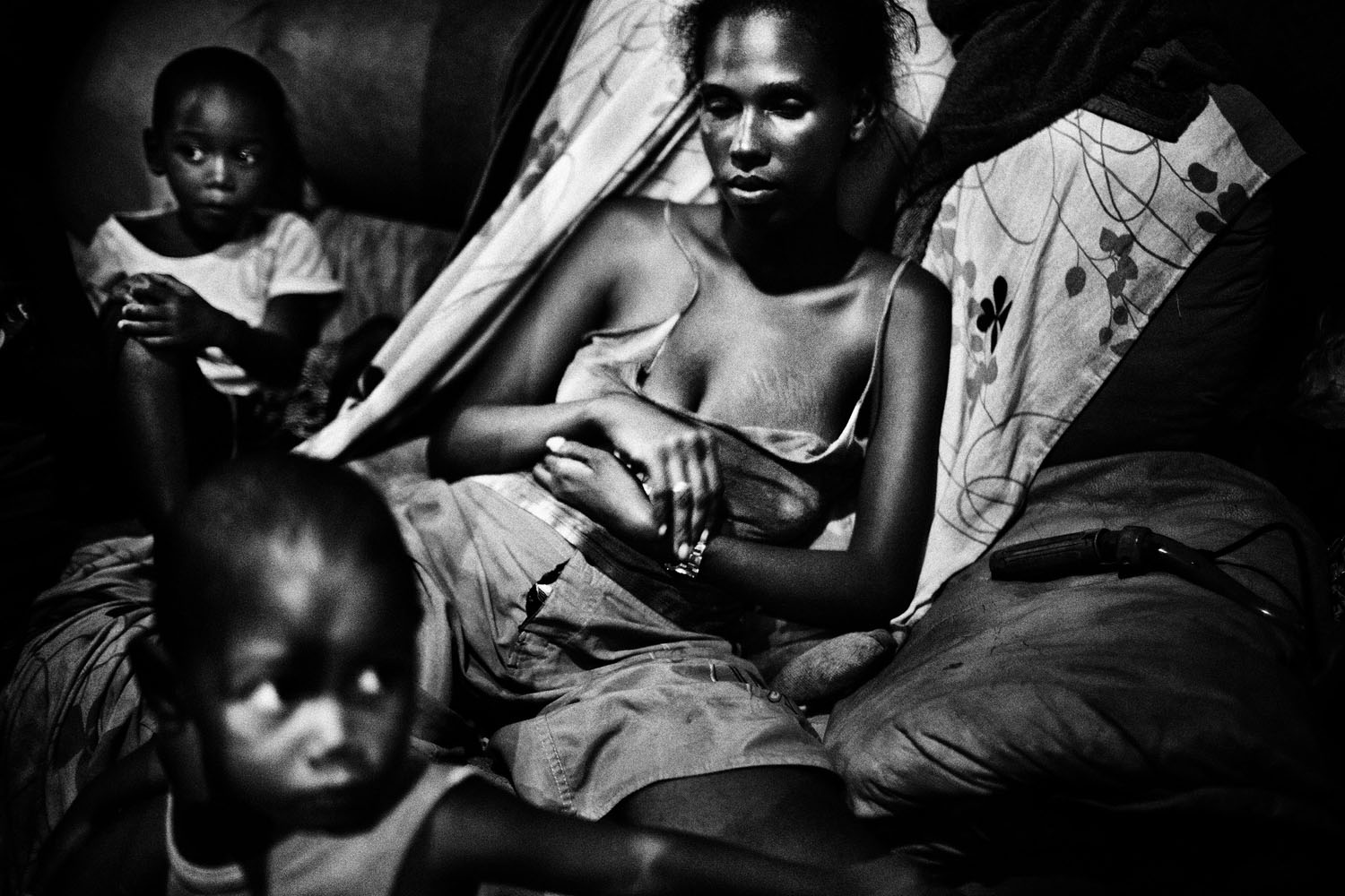 Melanie, 22, with her two sons in a small shack in an abandonated chocolate factory in Salvador de Bahia, Brazil. In spite of the extreme conditions in which they live, this factory ruin has become a home for the family. May 22, 2010.