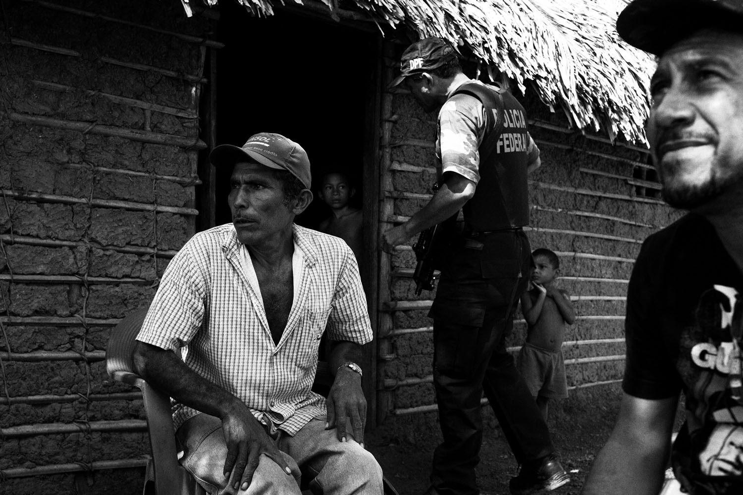Members of the special operation to free slave workers in the State of Maranhao talk with Rogerio. He and his family have been working for 13 years on the  fazenda  (farm) and have received no payment. Their  debt  and death threats prevent them from leaving. March 10, 2012.