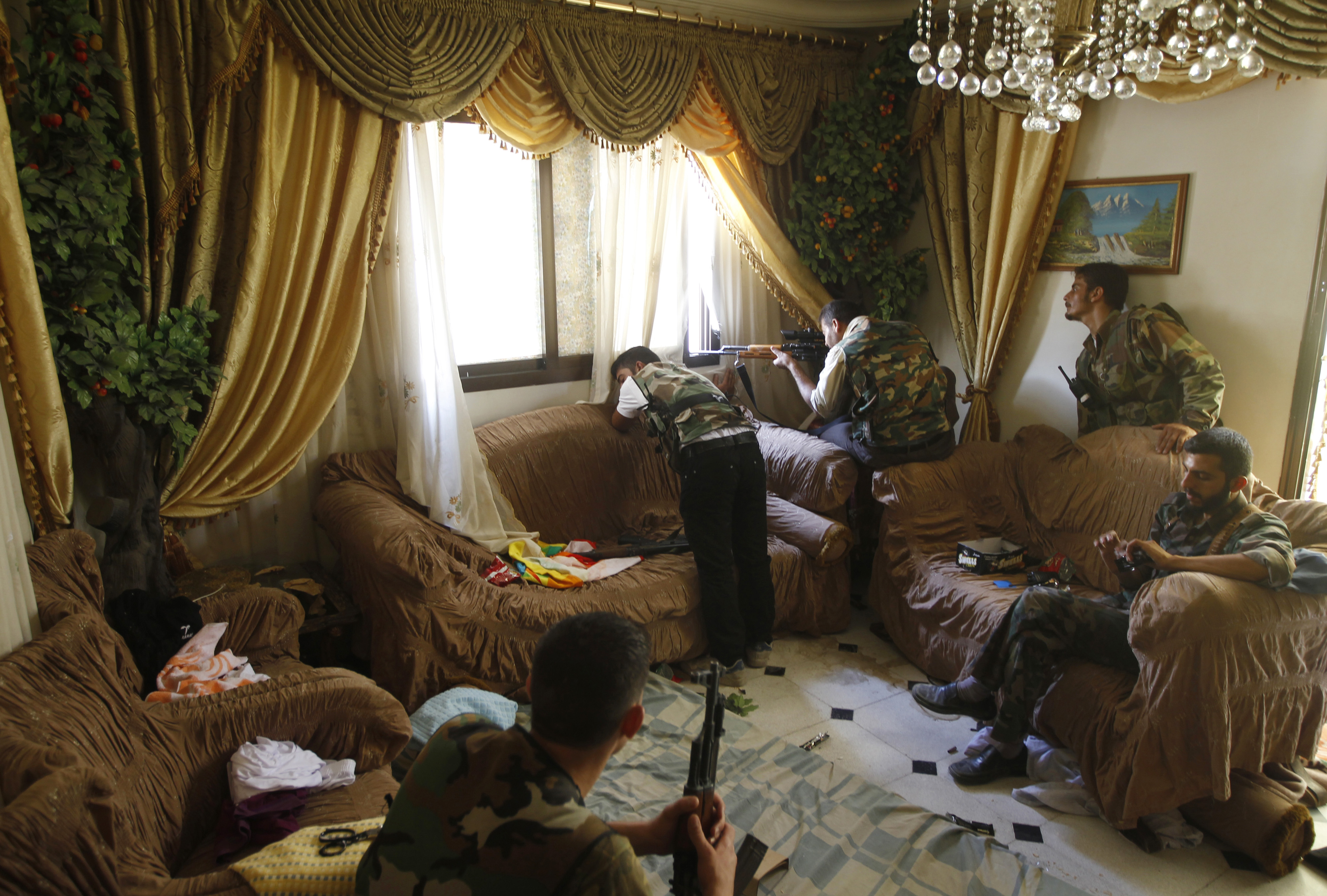 Goran Tomasevic                                                               I like these pictures where some fighters took up positions in a family living room. One rebel sat on the chair eating a chocolate bar as the commander looked out the window to scout the area beside a rebel firing from the window. They told me it was a former Syrian army position and they had killed three soldiers in the house — I could see a track of blood in the corridor. There was no one else in the house except the rebels.