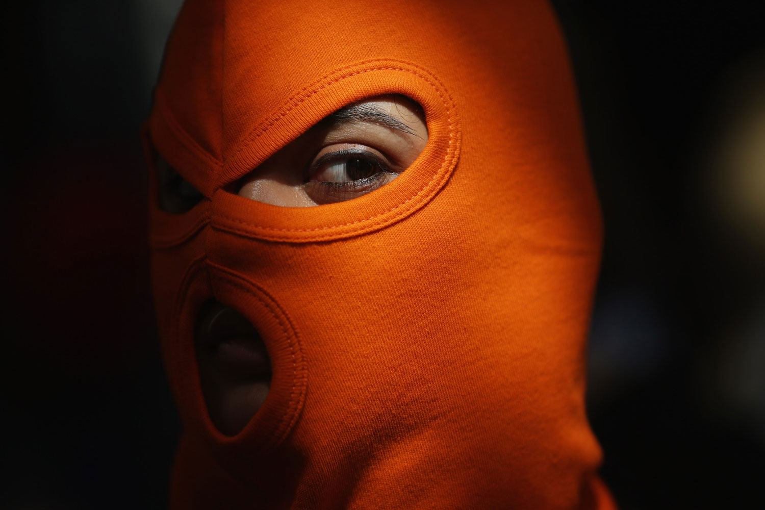 August 17, 2012. A person wears an orange mask as a demonstration by supporters of the jailed feminist punk band 'Pussy Riot' takes place outside the Russian Embassy on in London, England. The three women who staged an anti-Kremlin protest in a church in February, were found guilty of hooliganism motivated by religious hatred, and could face a three-year jail sentence.